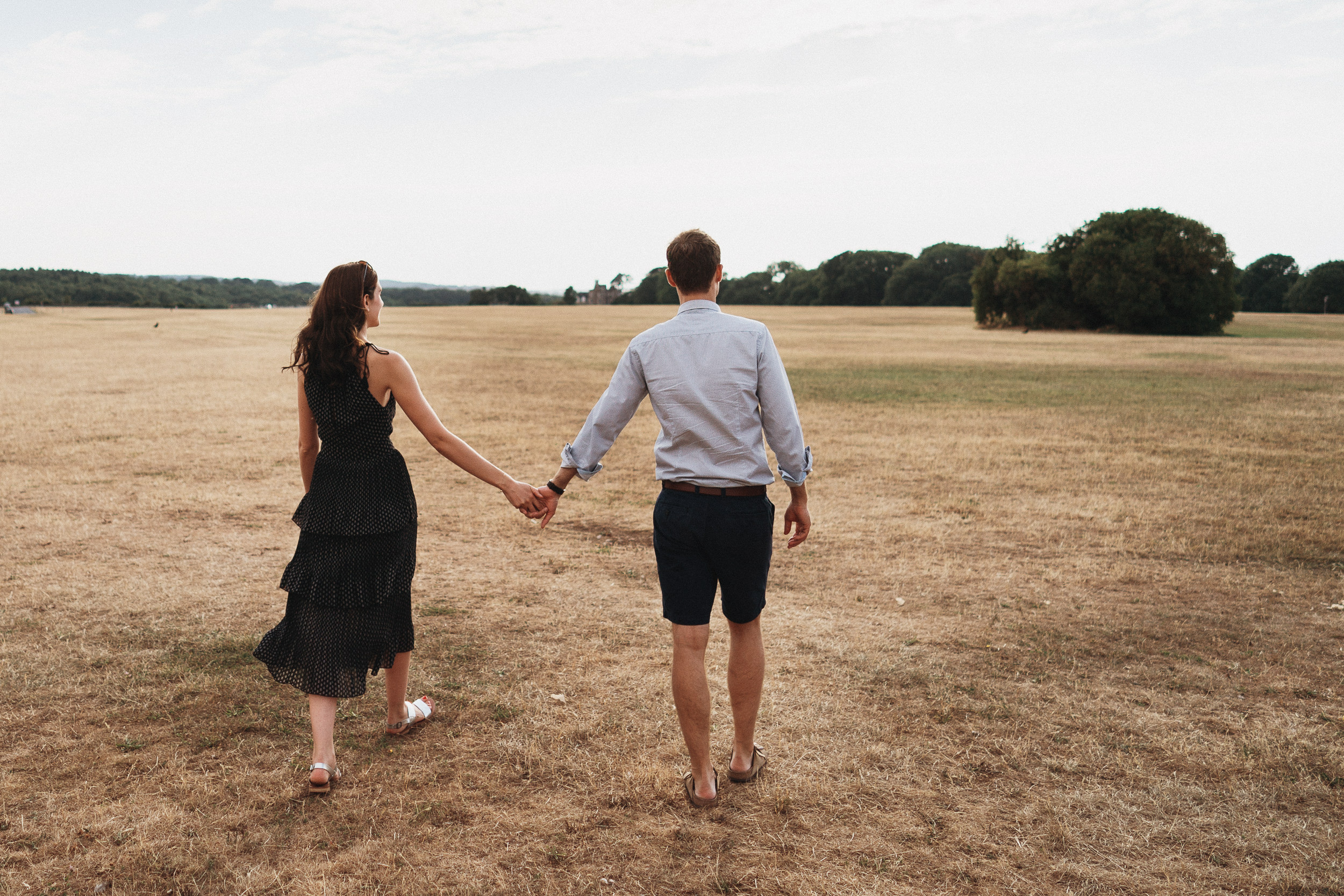 Engagement Shoot on Clifton Downs - The couple walking hand in hand across the Downs