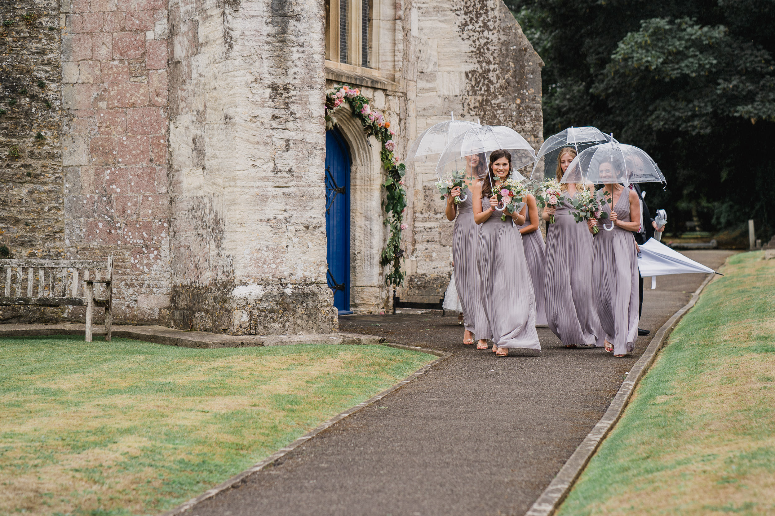 Orchardleigh Estate Wedding - Bridesmaids leaving the Church with Umbrellas
