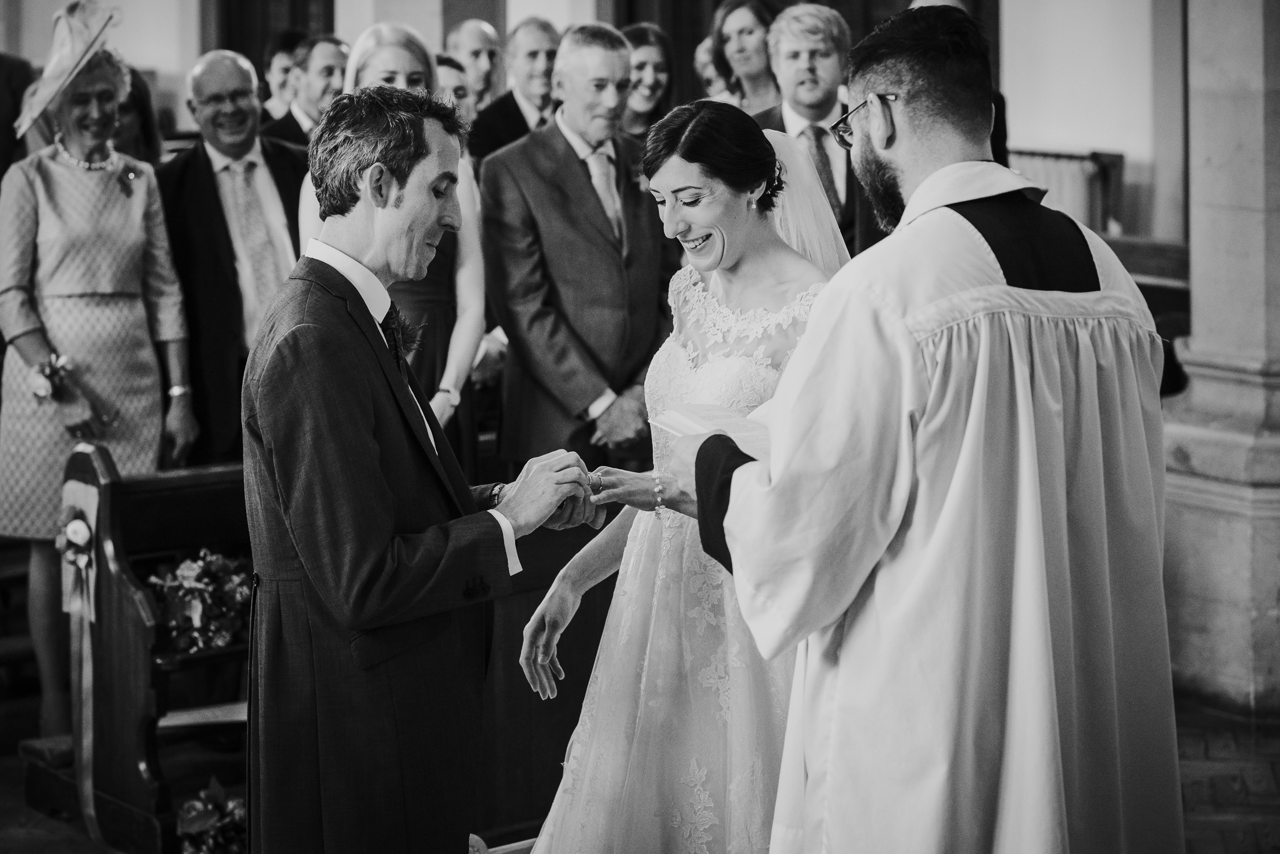 The Bride and Groom laughing as they struggle with the wedding ring
