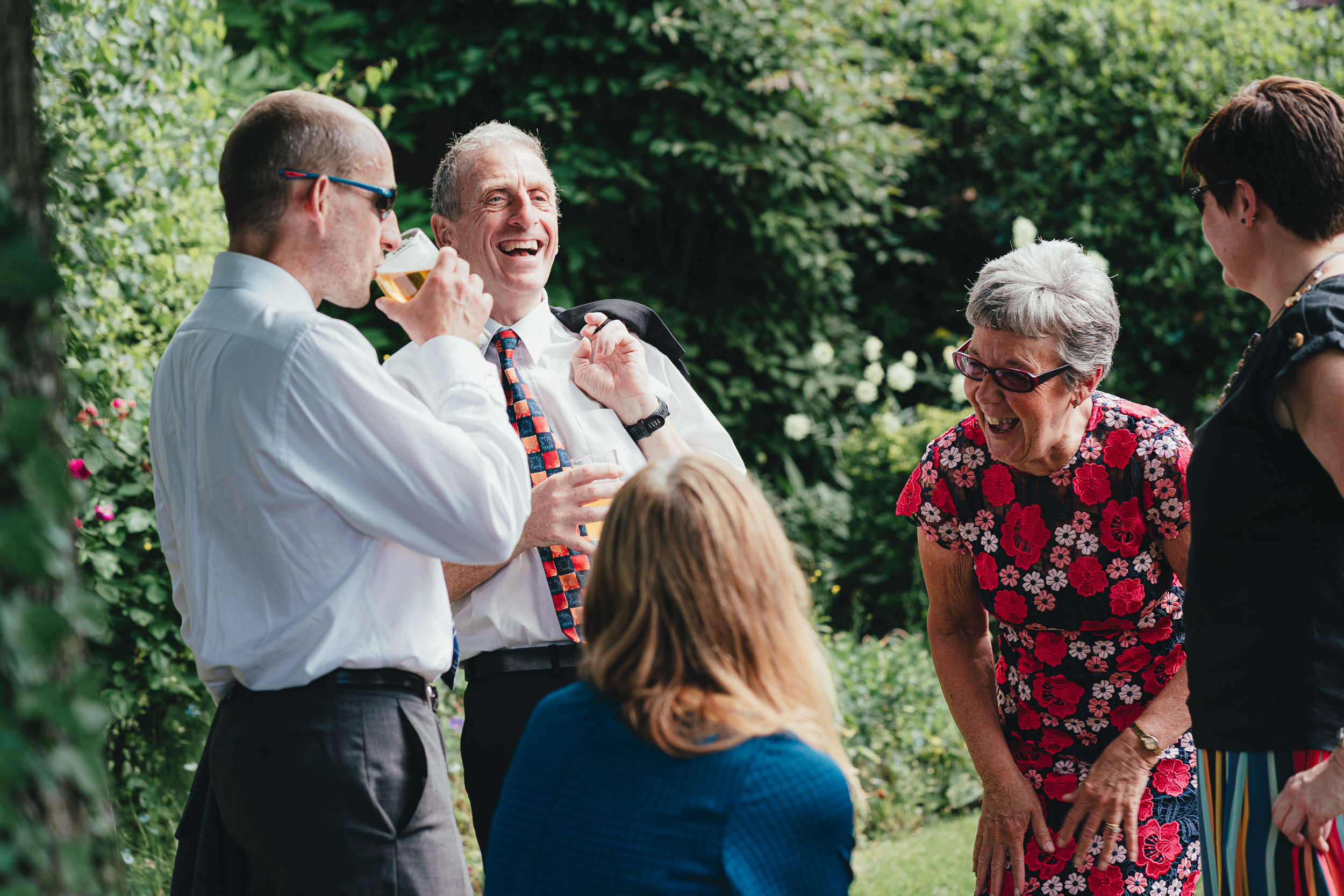 Wedding guests laughing in the garden of the Westbury on Trym village hall