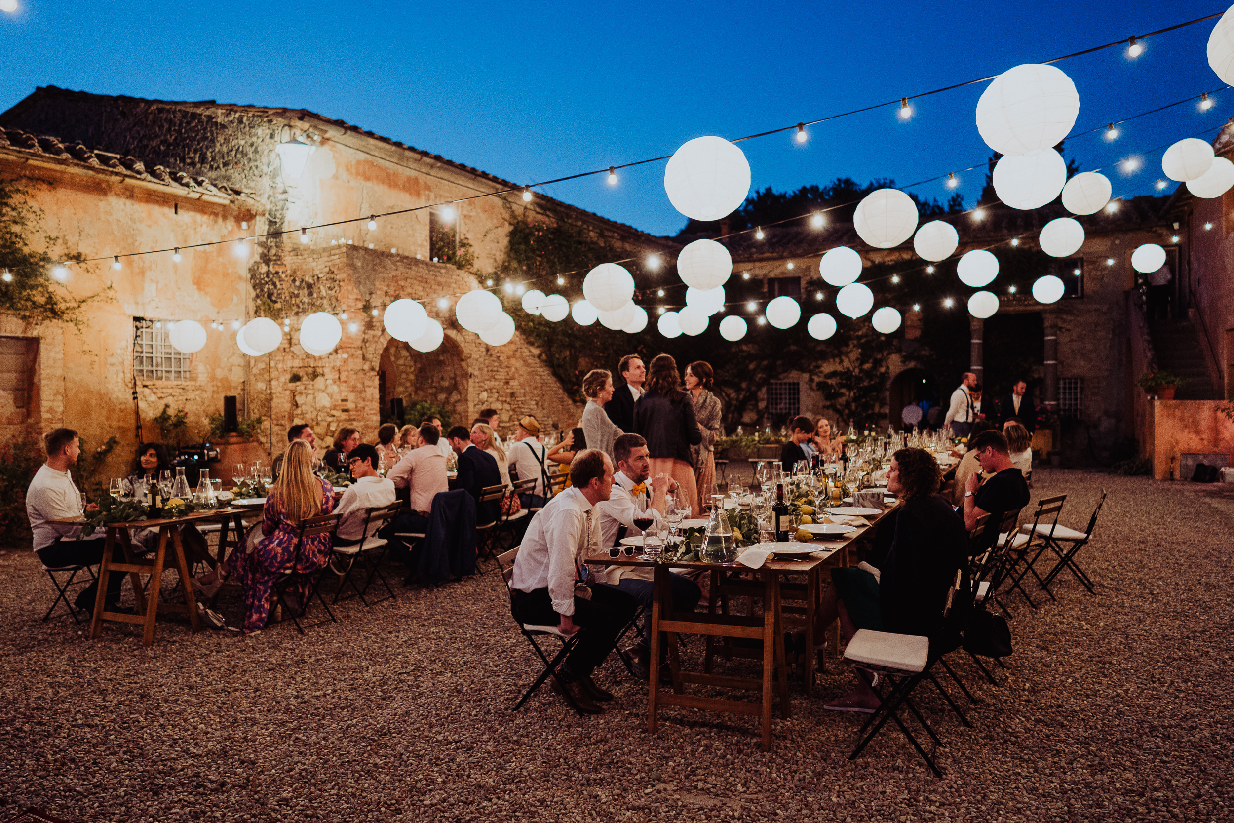 Tuscan Villa Wedding - guests eating outside in the courtyard at Villa Catignano
