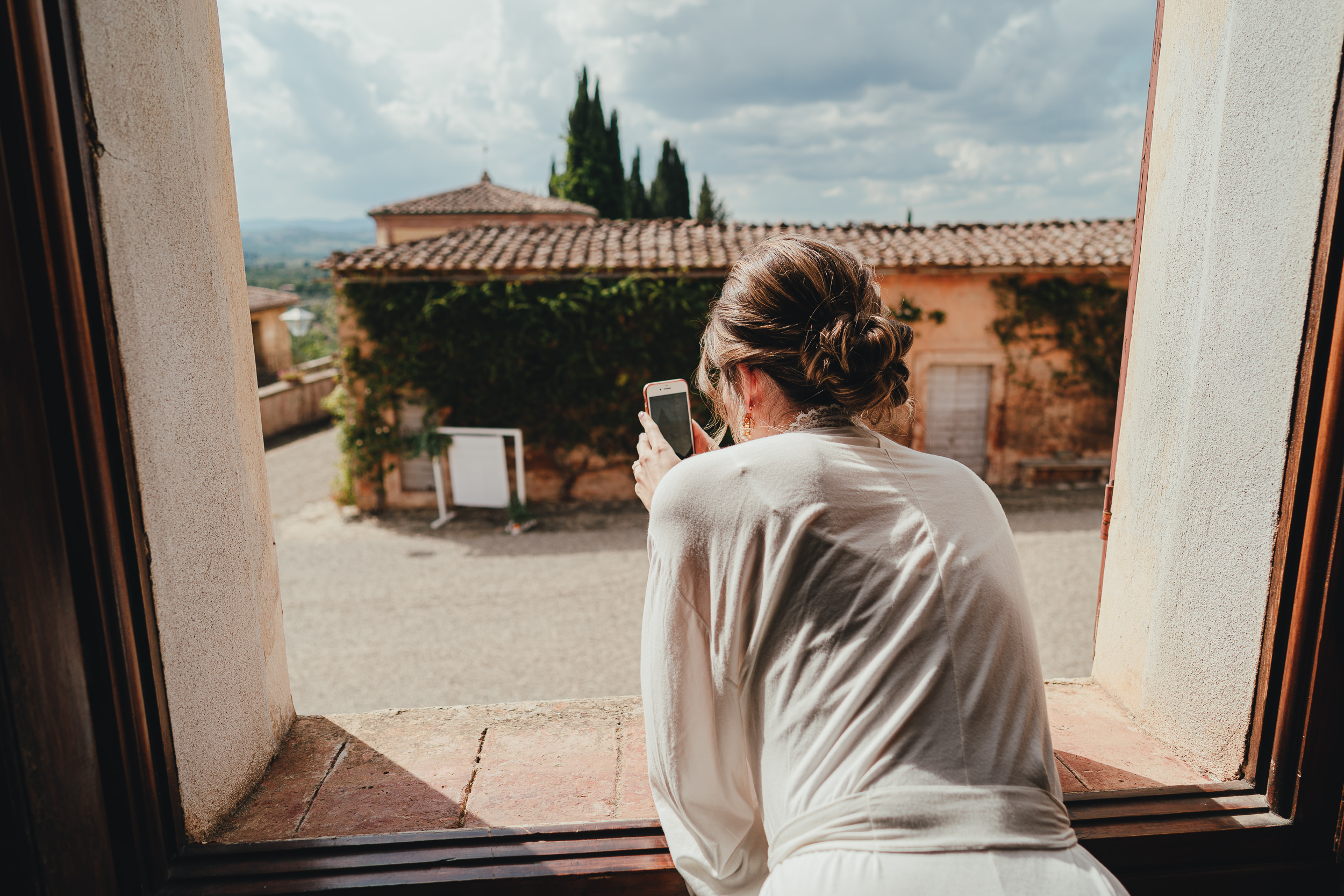 Tuscan Villa Wedding - The Bride takes photos out of the window