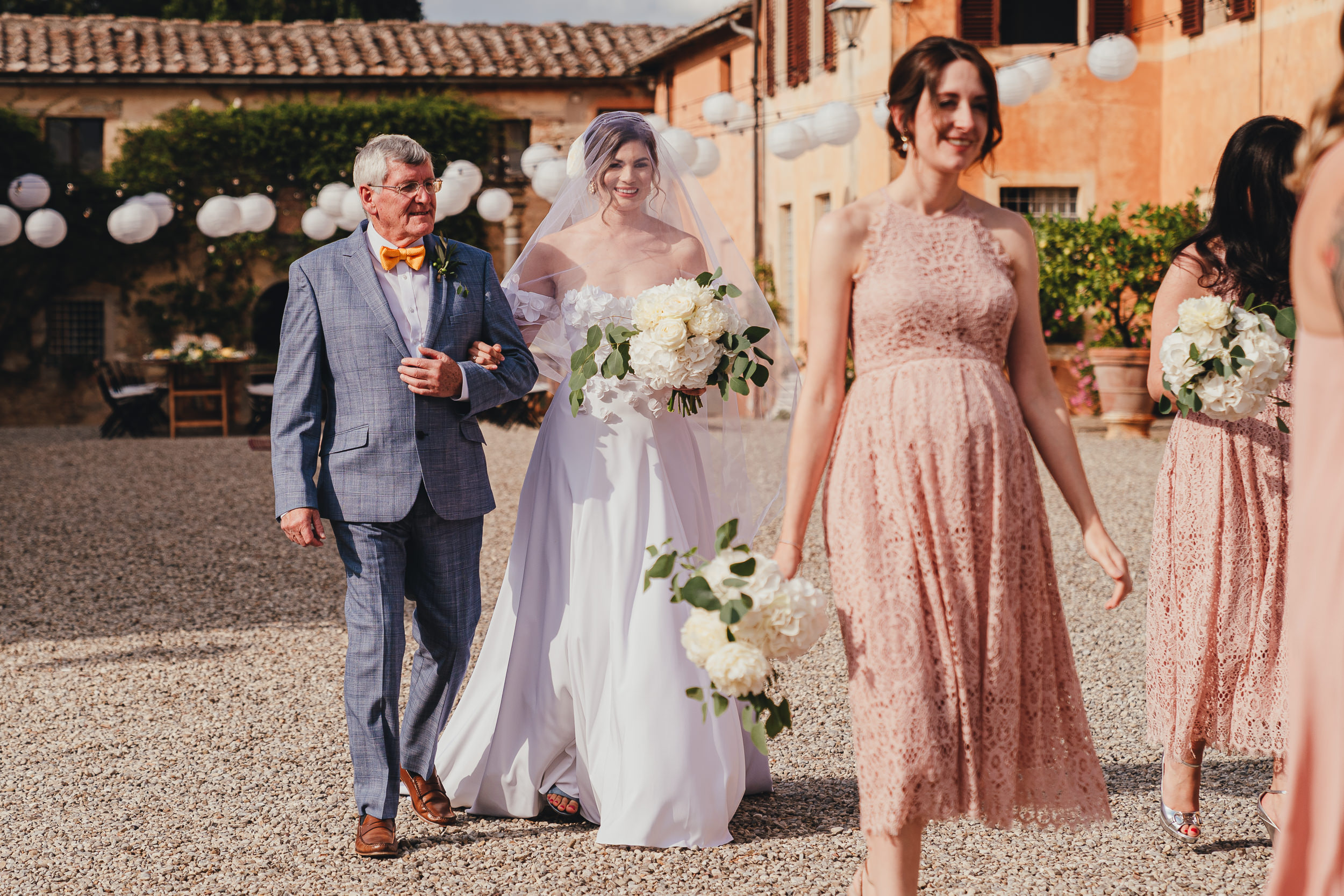 Tuscan Villa Wedding - The Bride walks to the ceremony with her Father and Bridesmaid