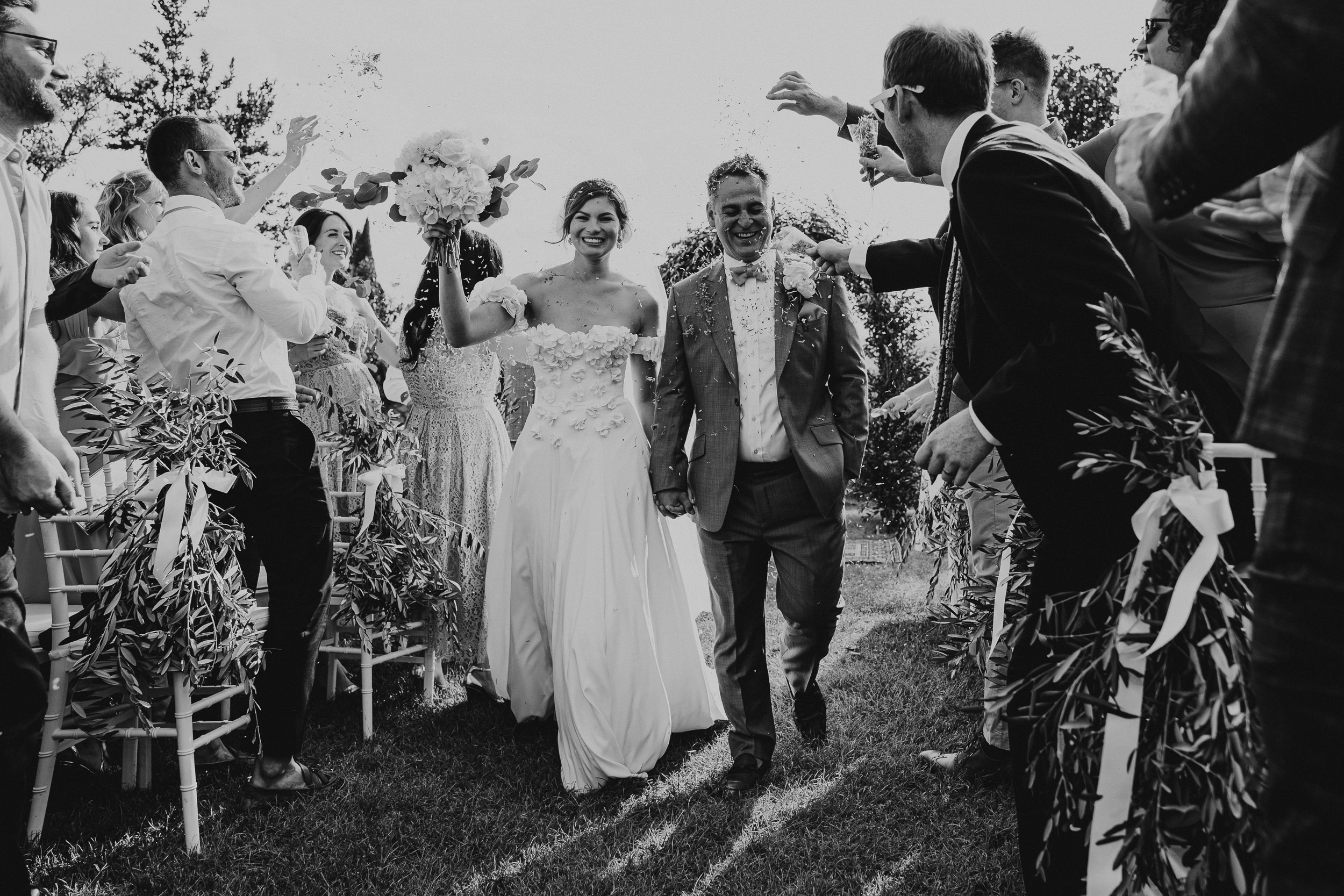 Guests throw confetti at the Bride and Groom