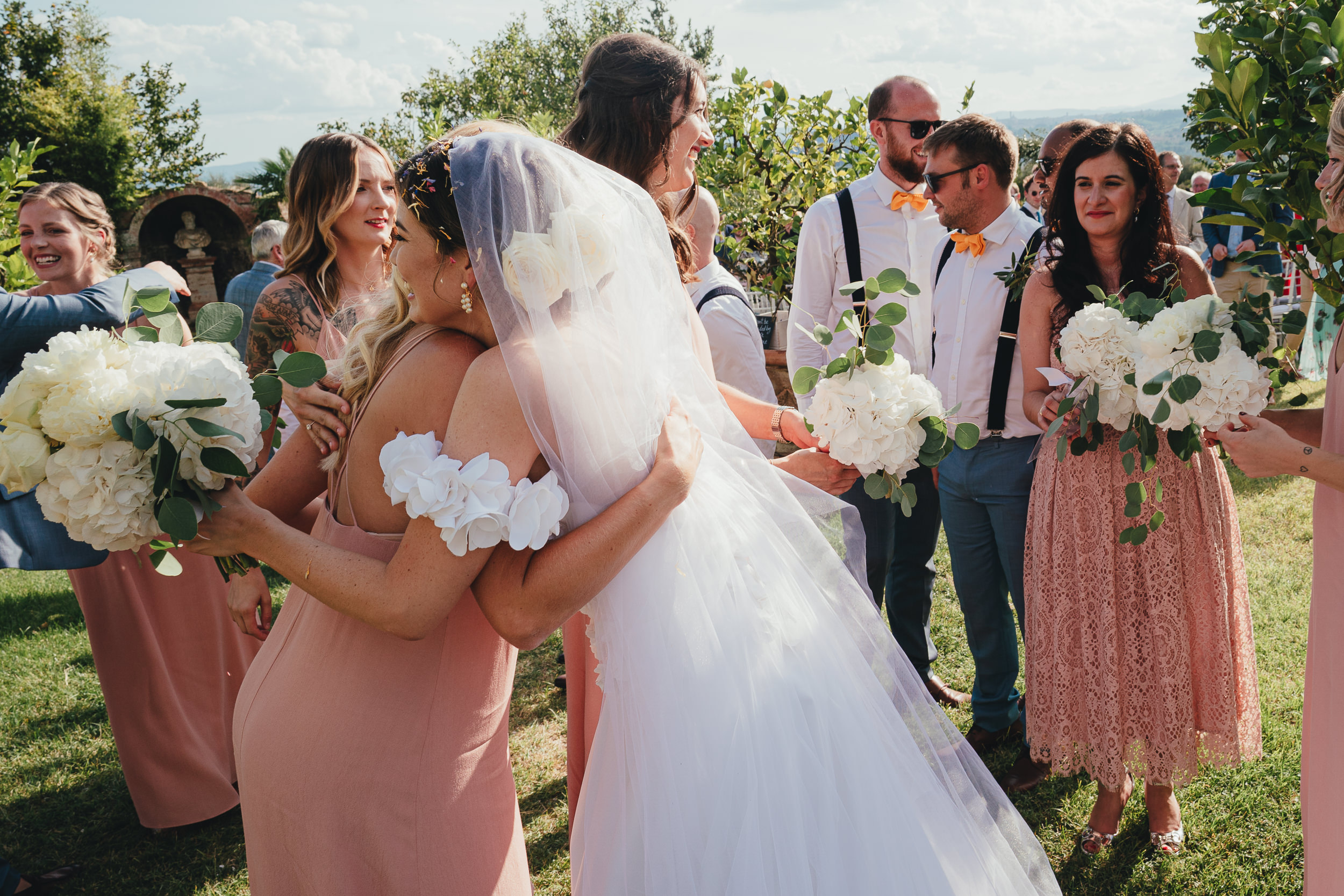 The Bride hugs her Bridesmaids in the garden at Villa Catignano