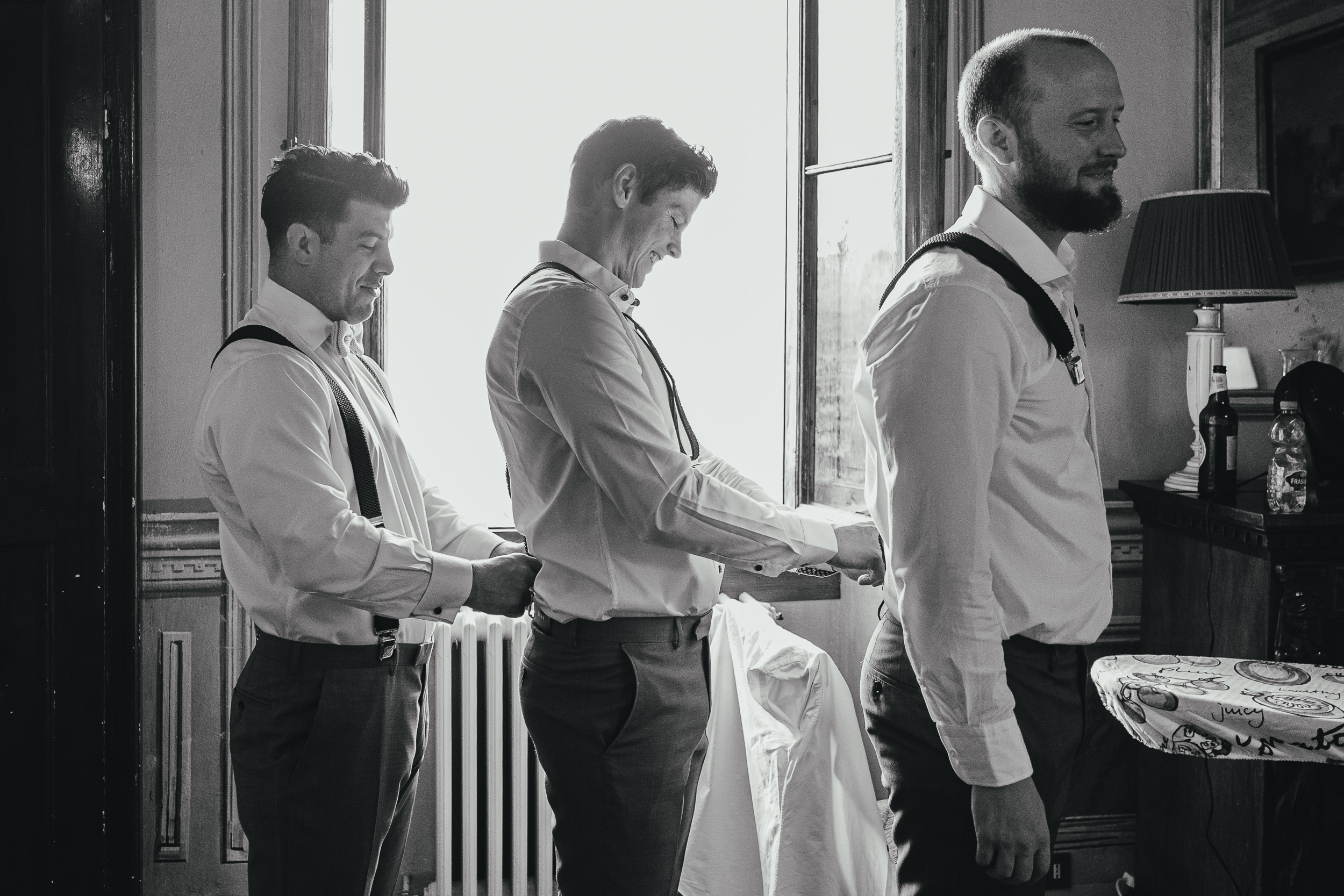 The groomsmen help each other put on their braces